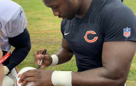 Chicago Bears linebacker Roquan Smith signs Simons' football. Smith's autograph can go for $129.