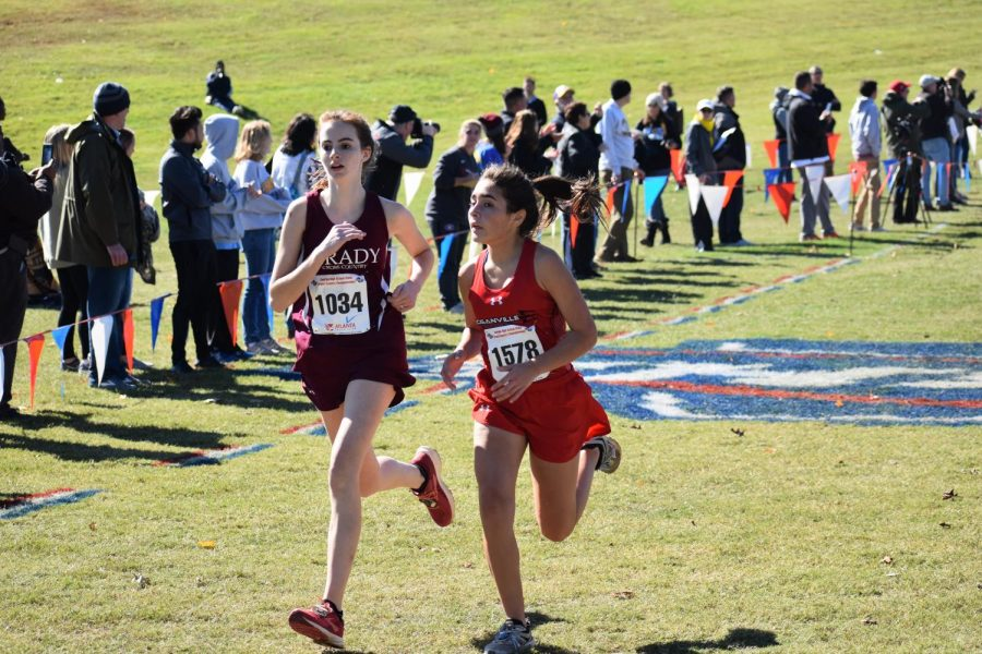 Junior Elena hubert chases down a competitor from Loganville in the final yards of the state 5A meet. Hubert finished 64th overall and fourth for the Knights.