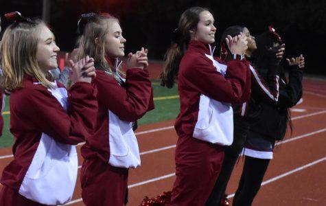 (Left to right) Junior Kristen Hart, senior Olivia Ledbetter and Junior Madigan Duncan cheer at the Knights' last football game of the season on Nov. 9.