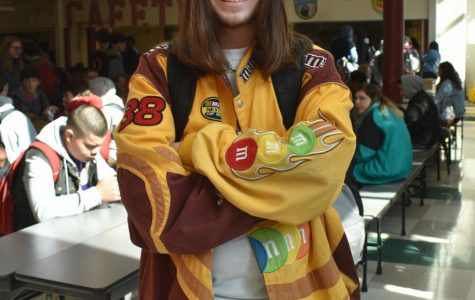 Freshman Sam Offutt smiles in the lunchroom, wearing a yellow jacket covered in patches and tinted sunglasses to match.