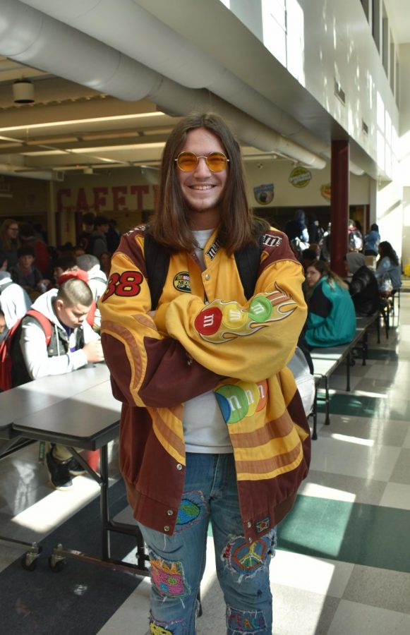 Freshman+Sam+Offutt+smiles+in+the+lunchroom%2C+wearing+a+yellow+jacket+covered+in+patches+and+tinted+sunglasses+to+match.