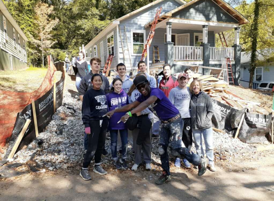 Home buyer Joel Summer stands in front of his new home alongside student volunteers from different high schools, including Marist and Riverwood. Habitat for Humanity has been offering high school builds for many years, and Summer's was the first one the Grady chapter was invited to attend.
