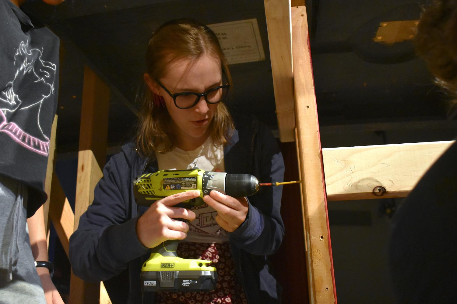 Senior+Elise+Livius+screws+two+wood+planks+together+for+a+set+structure+using+an+electric+screwdriver.+Livius+is+master+carpenter+on+the+crew.