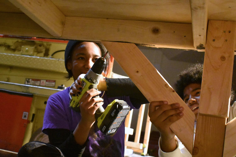 Freshman+Naiomi+Partridge+and+freshman+Quavion+Turner+screw+in+a+wood+piece+to+construct+a+platform.