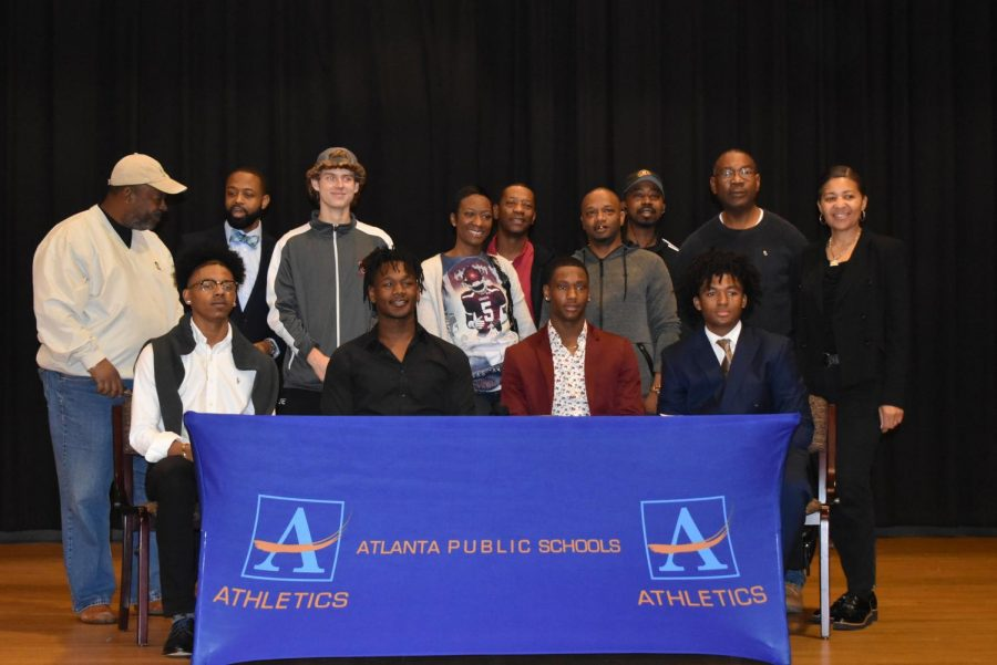 On+Feb.+5%2C+APS+Signing+Day+took+place+at+Therrell+High+School.+The+four+football+players+who+signed+smile+after+they+make+it+official.