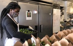Avalon Catering's Pastry Chef, Sitara Ward, fills up boxes with mixed greens which are to be sent out to health care workers.