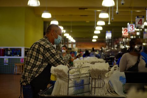 An employee bags groceries at the Buford Highway Farmers Market on April 17. According to the Washington Post, at least 41 grocery store workers across the country have died due to the coronavirus and thousands more have tested positive despite protective gear, capacity restrictions and temperature checks.