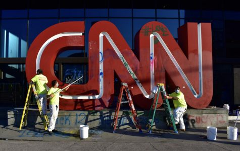 Workers scrub off graffiti from the CNN sign.