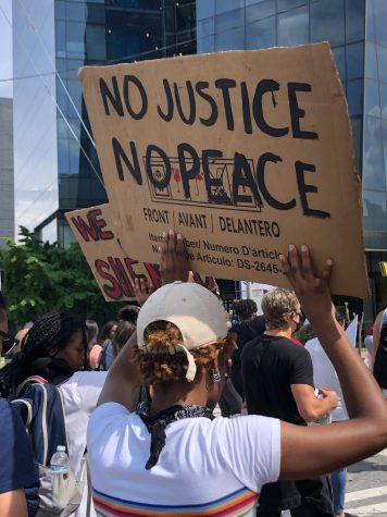 """A participant of the March 29 protest against police brutality holds a sign saying """"No Justice, No Peace."""""""
