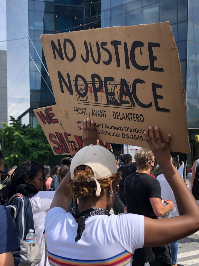 A+participant+of+the+March+29+protest+against+police+brutality+holds+a+sign+saying+%22No+Justice%2C+No+Peace.%22