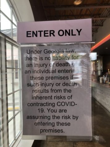 A poster on the front door of Little Rey reads that the guests are assuming the risks of Covid-19 by entering the restaurant.
