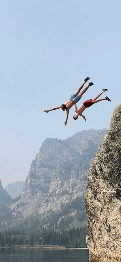Shevlin and Harrison jump off a rock into Phelps Lake, located in Grand Teton National Park