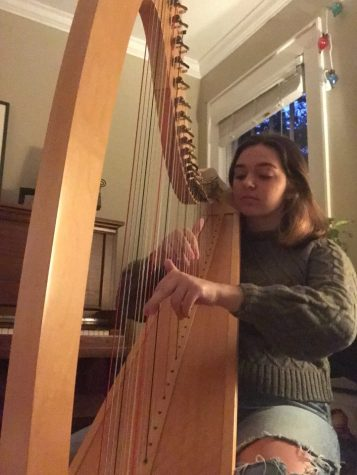 Junior Della Goines sits at home, practicing her harp. Goines misses being able to perform in front of an audience due to the COVID-19 pandemic.