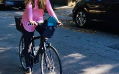 Junior Nora Ball rides her bike down a street. She is participating in Biketober, an event spanning the month of October, that encourages people to bike as much as possible.