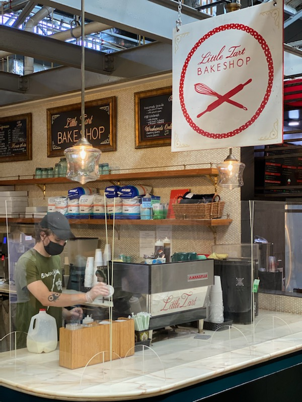 A masked employee makes a coffee behind a plexiglass barrier at Little Tart Bakeshop in Krog Street Market. These changes have been put into place to minimize contact between employees and customers.