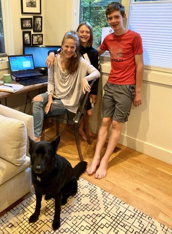 Carter and her kids pose in front of her work space set up with their dog.