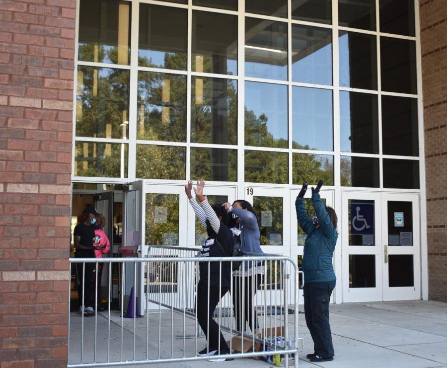 Poll workers at Bunche Middle School cheer on voters.