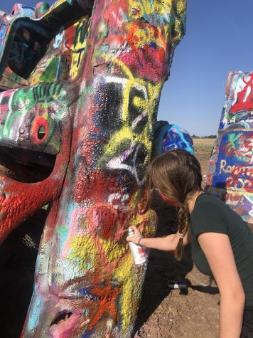 Junior Ella Mitchell doodles a heart with spray paint on to the Cadillac Ranch in Armarillo, TX. Cadillac Ranch is a public art sculpture that allows anyone to add to the car sculptures.