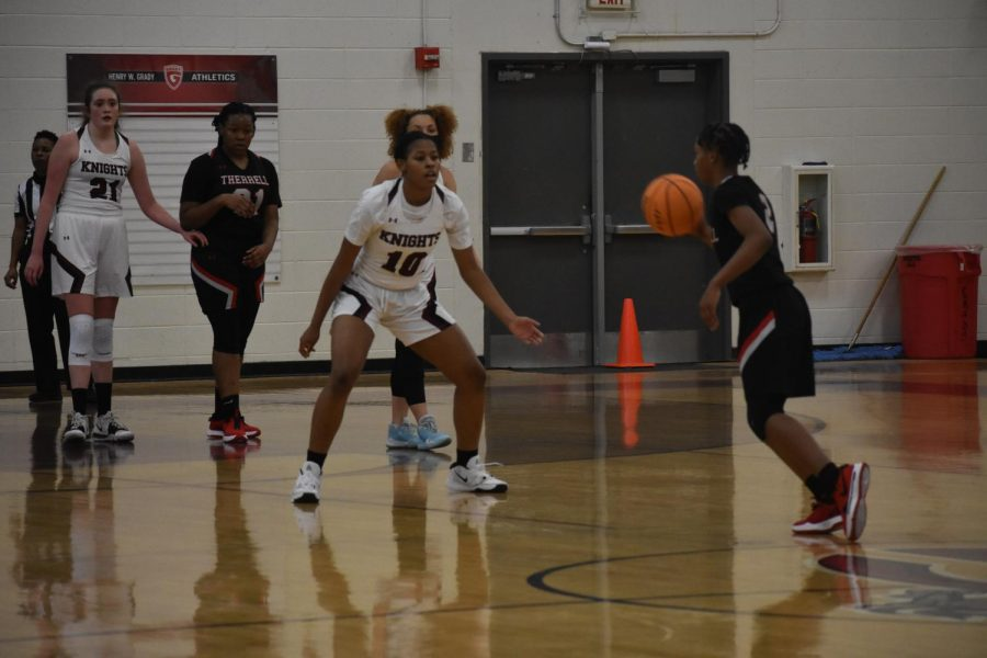 Gradys defense prepares as Therrells point guard dribbles the ball up the court.
