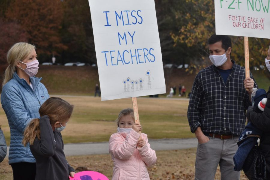 """A young girl holds up a sign that reads, """"I Miss My Teachers"""". According to parents of students who are not back for face-to-face learning, teachers are not the only thing their kids are missing. They are also missing out on hands-on learning and socializing with their friends."""