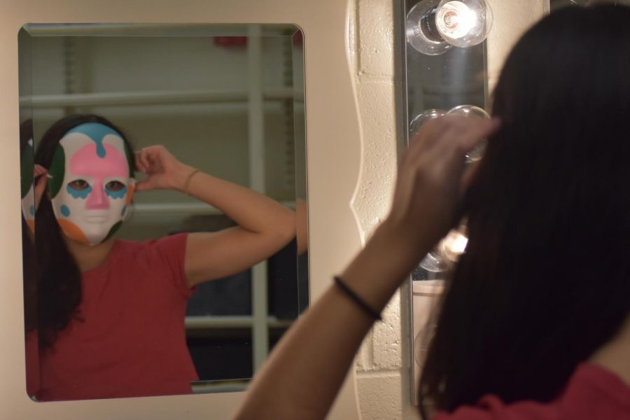 Senior Emilia Gustafson, who portrays Mrs. Zamora, adjusts the mask she will perform in. All cast members participating in the in-person recording of