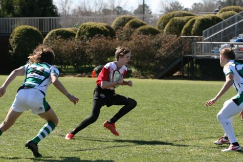 Abbott is seen running with the ball in a match. Abbott started playing rugby in seventh grade.
