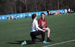 Keely Baker kneels with a member of the opposing team during a match.