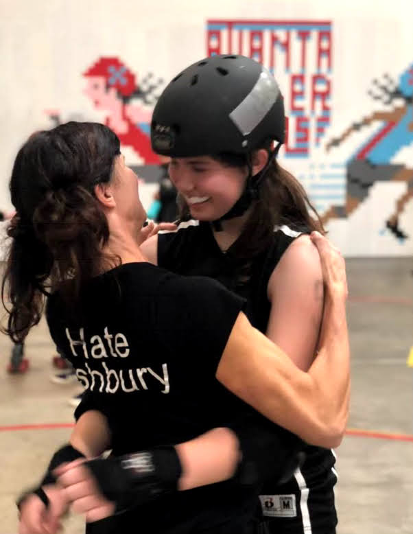 Brattain (right) hugs her mother after a roller derby match.