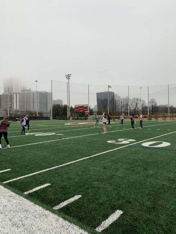 The Girls Lacrosse team warms up for a Friday practice, safety distanced.
