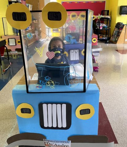 DeAndre Mahone Jr., a kindergartener at Hope Hill Elementary school, works at his classroom desk. His teacher decorated her students desk shields like cars.