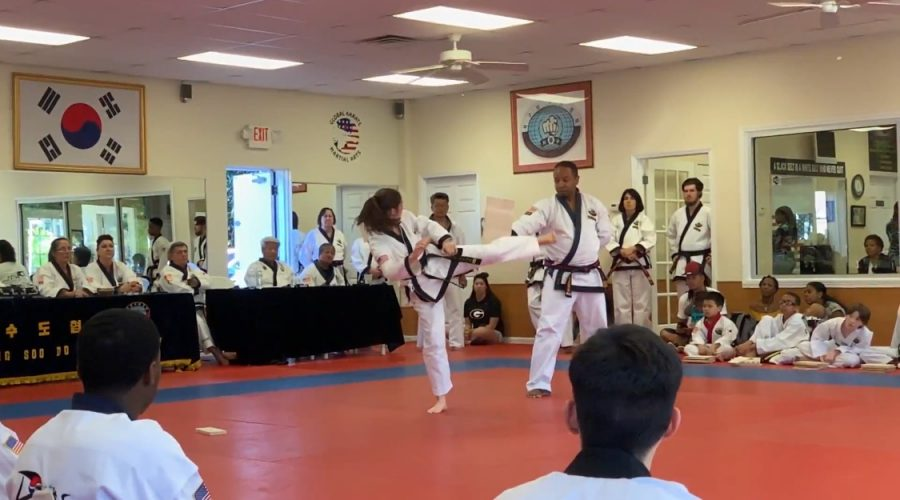 Pruitt is completing her third degree blackbelt test by breaking a board with a spinning hook kick.