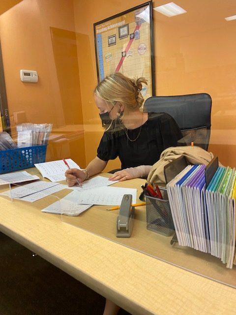 Kumon employee Audrey Isakov grades students work.
