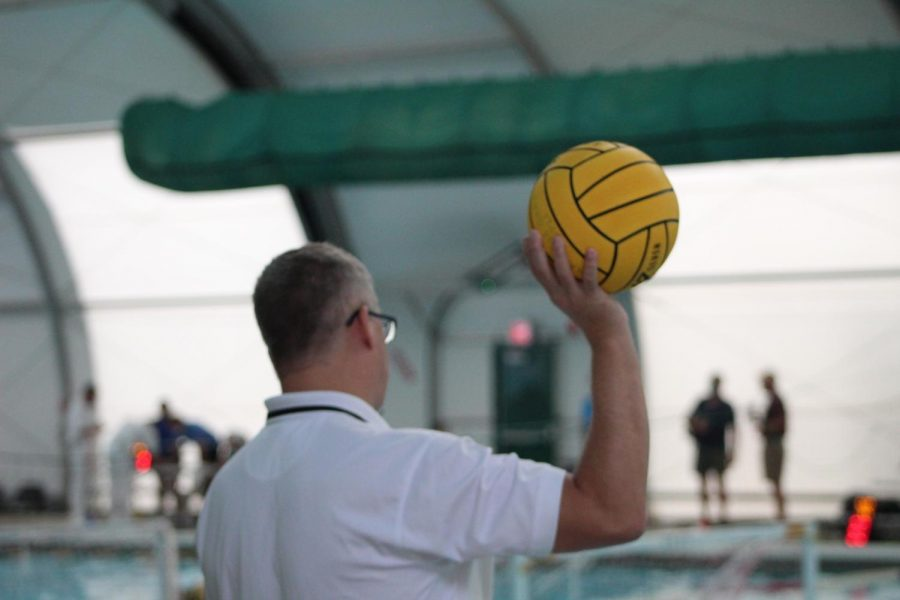 A water polo referee holds a ball during timeout.