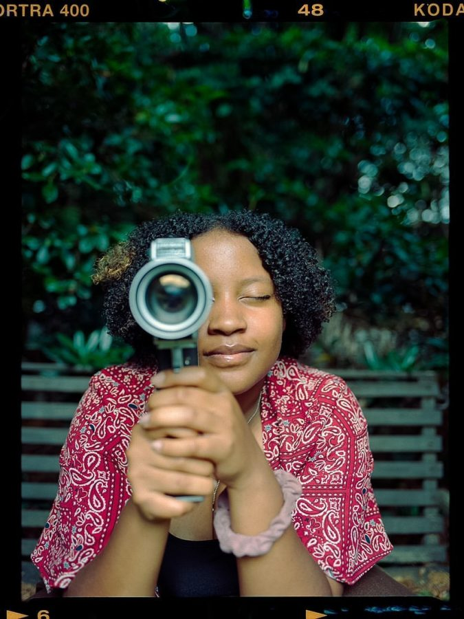 Alaya Foote poses in a photo on traditional film with a camera.